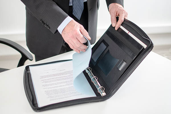 Policy document being taken out of a briefcase.
