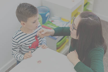 A speech and language therapist works with a small boy.